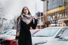 Jeune blonde heureuse de femme dans un manteau noir et des promenades d'écharpe par la ville Se réunir de attente photographie stock