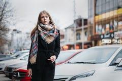 Jeune blonde heureuse de femme dans un manteau noir et des promenades d'écharpe par la ville Se réunir de attente image libre de droits