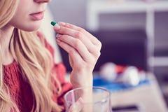 Jeune blonde mignonne prenant une pilule avec un verre de l'eau à la maison photographie stock
