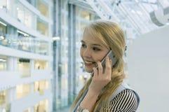 jeune blonde parlant au téléphone sur le fond des planchers d'un centre commercial moderne profondeur de champ, tache floue photos stock