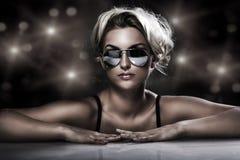 Jeune blonde utilisant les lunettes de soleil élégantes Image libre de droits