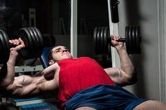 Jeune bodybuilder faisant le banc à presse pour le coffre photo stock