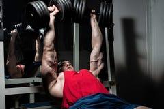 Jeune bodybuilder faisant le banc à presse pour le coffre photo libre de droits