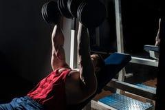 Jeune bodybuilder faisant le banc à presse pour le coffre photos libres de droits