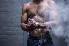 Jeune Bodybuilder secouant la craie outre de ses mains Photographie stock