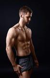 Jeune bodybuilder sur un fond noir images libres de droits