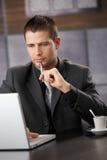 Jeune bossage travaillant sur l'ordinateur portatif dans le bureau de fantaisie Photos libres de droits