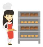 Jeune boulanger féminin heureux tenant le plateau du pain Photos stock
