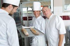 Jeune boulanger montrant le pain de plateau dans la boulangerie de cuisine photos stock