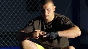 Jeune boxeur enveloppant des bandages sur sa main avant combat dans le gymnase lentement banque de vidéos