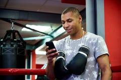 Jeune boxeur professionnel avec un téléphone dans l'anneau sur le fond du gymnase avec des sacs photo stock