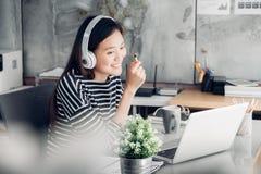 Jeune bras occasionnel asiatique de femme d'affaires sur la pose de repos de bureau avec le lapt images stock