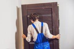 Jeune bricoleur installant la porte avec une mousse de support dans une chambre image stock