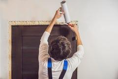 Jeune bricoleur installant la porte avec une mousse de support dans une chambre photos stock
