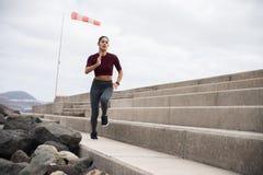 Jeune brune attrayante fonctionnant rapidement sur des escaliers Image libre de droits