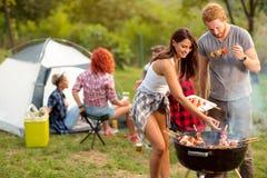 Jeune brune avec la portion d'ami sur le barbecue de plat Image libre de droits