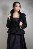 Jeune brune avec les cheveux rassemblés dans une robe et une veste foncées de plaid avec le haut collier se tenant sur le fond gr Photos stock