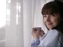 Jeune brune avec une tasse de café par la fenêtre regardant dans la caméra image libre de droits