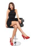 Jeune brune caucasienne magnifique dans la robe noire sur la chaise Images stock