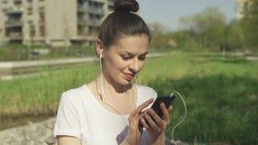 Jeune brune dans des écouteurs utilisant le smartphone banque de vidéos