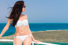 Jeune brune dans le maillot de bain se tenant sur le yacht à un résumé ensoleillé Photographie stock