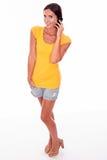 Jeune brune de sourire avec le téléphone portable Photo stock