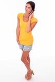 Jeune brune de sourire avec le téléphone portable Image libre de droits