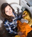 Jeune brune faisant la blanchisserie dans la cuisine et le sourire Images libres de droits