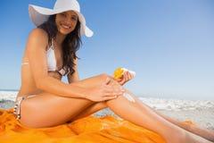 Jeune brune gaie avec le chapeau de paille mettant sur la crème du soleil Image libre de droits
