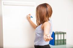 Jeune brune posant une question à sa classe Photographie stock libre de droits