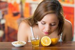 Jeune brune se pliant au-dessus de la table sentant le citron coupé en tranches, le verre de miel et de la granola du côté Photos stock