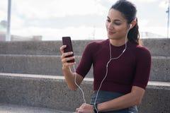Jeune brune sportive avec le téléphone portable images libres de droits