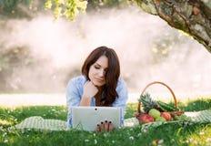 Jeune brune surfant le Web en parc sur un backgroun brumeux Photos libres de droits