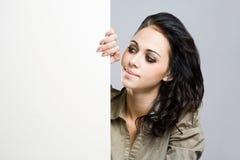 Jeune brunette attirant retenant le panneau-réclame blanc. Image libre de droits