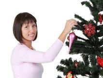 Jeune brunette décorant l'arbre de Noël Images stock