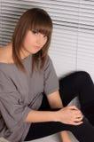 Jeune brunette dans une robe grise Images stock