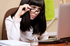 Jeune brunette travaillant avec l'ordinateur portatif Photographie stock