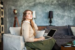 Jeune bureau de Woman Sitting de concepteur à la maison avec l'ordinateur portable photo stock