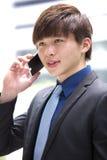 Jeune cadre commercial masculin asiatique à l'aide du téléphone intelligent Photographie stock