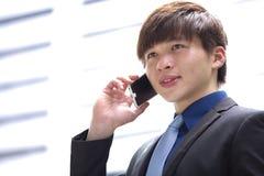Jeune cadre commercial masculin asiatique à l'aide du téléphone intelligent Photos stock