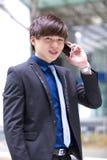 Jeune cadre commercial masculin asiatique à l'aide du téléphone intelligent Photos libres de droits