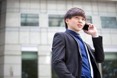 Jeune cadre commercial masculin asiatique à l'aide du téléphone intelligent Photo libre de droits