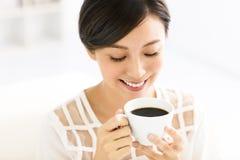 Jeune café potable de sourire de femme pendant le matin Photographie stock libre de droits