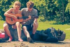 Jeune camping de couples jouant la guitare extérieure Images libres de droits
