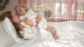 Jeune caresse de m?re sa fille adorable d'enfant en bas ?ge Les filles aimantes ont l'amusement dans le lit banque de vidéos