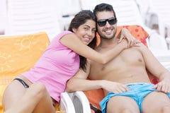 Jeune caresse heureuse de couples heureuse avec amour sur la plage Image libre de droits