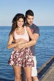 Jeune caresse heureuse de couples heureuse avec amour sur une plage de mer Photos libres de droits