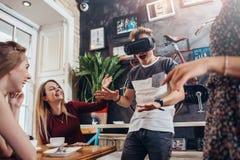 Jeune casque de réalité virtuelle d'essai de type criant jouant le jeu effrayant tandis que son rire assez femelle gai d'amis Photo libre de droits