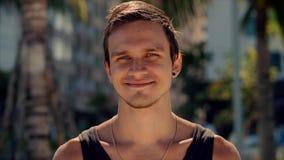 Jeune Caucasien de portrait haut étroit d'homme bel de brune une barbe regardant dans les sourires de caméra, sur le fond de ciel banque de vidéos