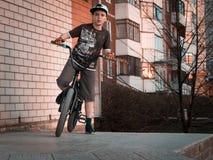 Jeune cavalier de bmx de garçon sur une rampe avec le fond urbain au coucher du soleil Photo stock